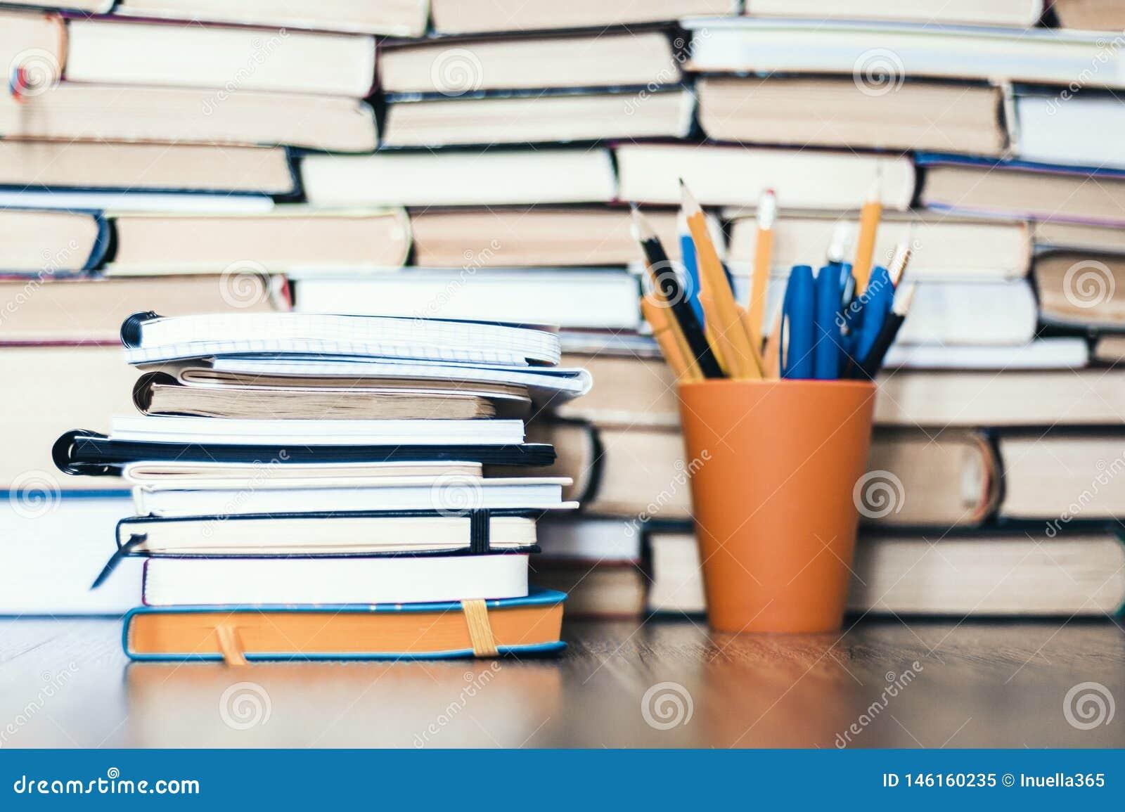 堆书、笔记本和铅笔在塑料持有人在木桌上与拷贝空间文本的