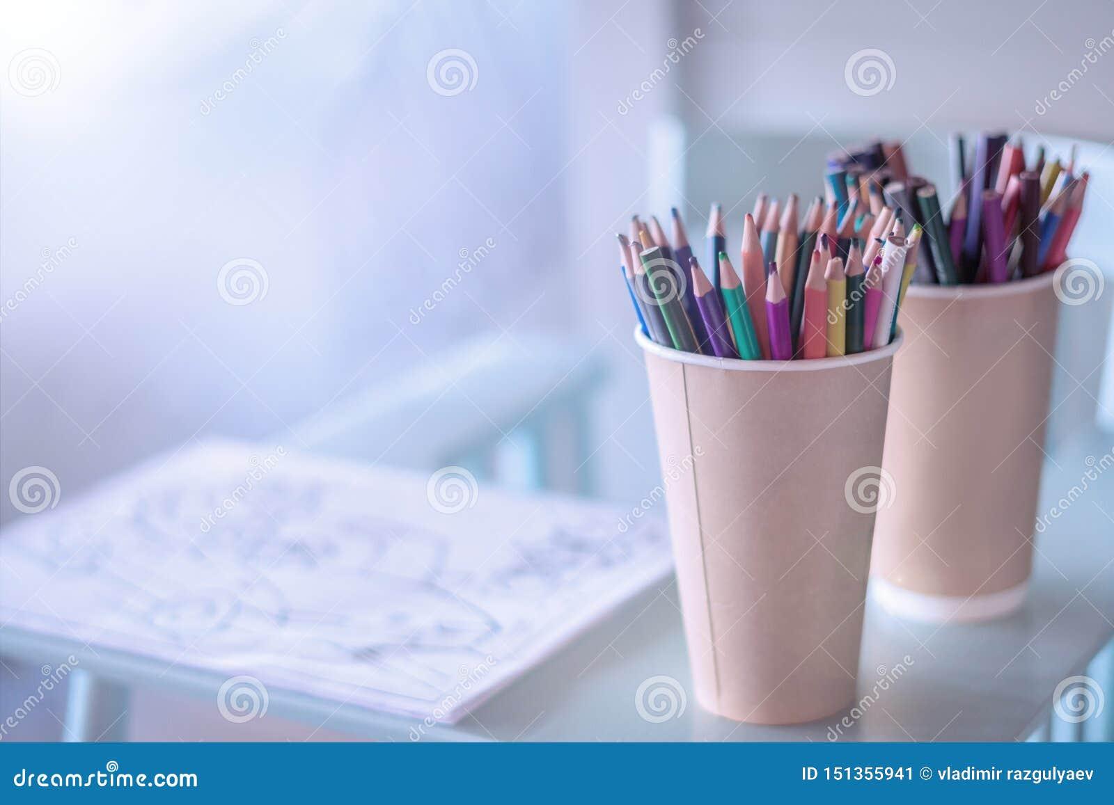 堆在一块玻璃的色的铅笔在木背景,顶视图 画的一个舒适地方为孩子