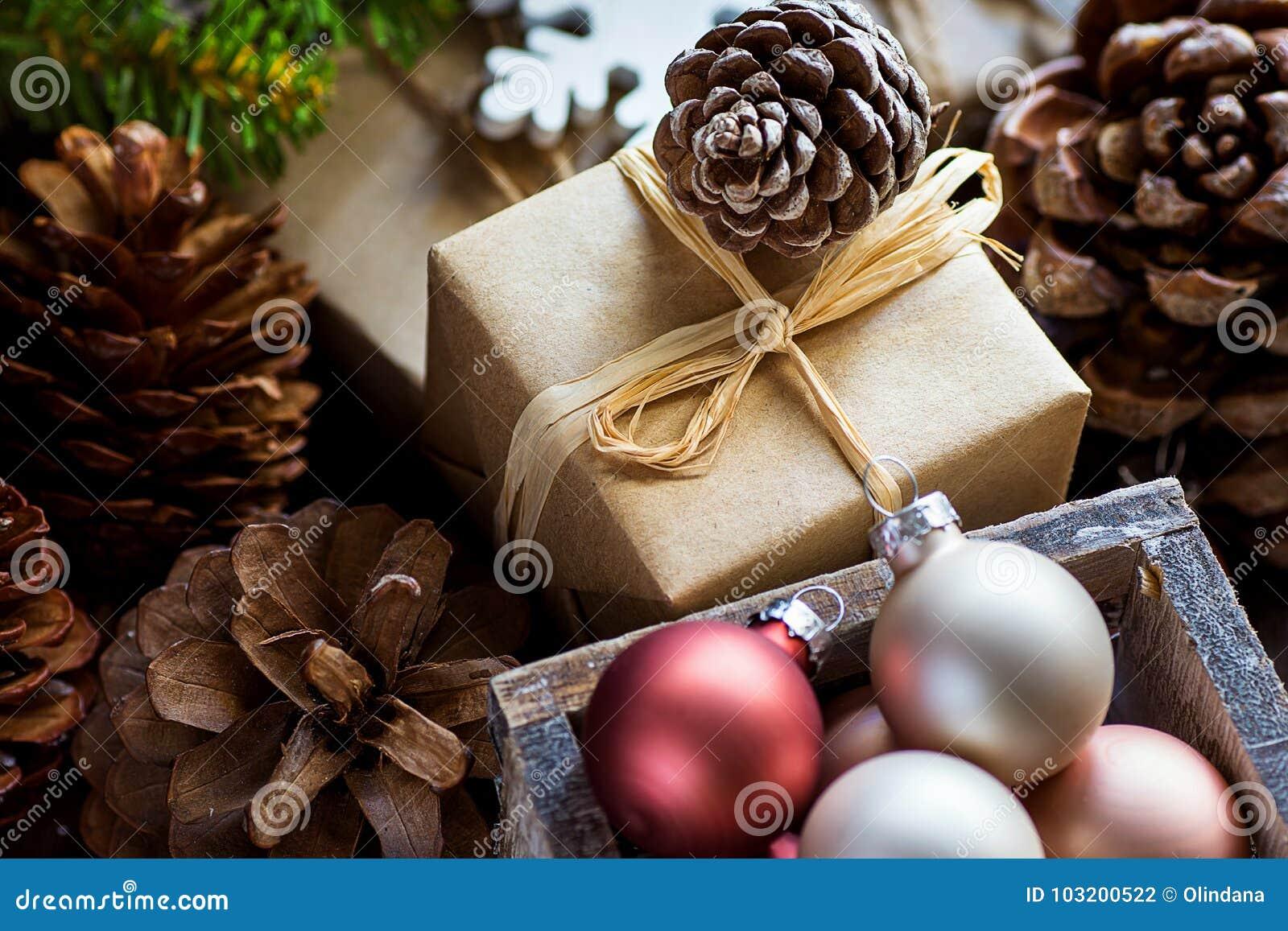 堆在工艺纸五颜六色的球大杉木锥体绿色杉树分支雪剥落包裹的圣诞节和新年礼物盒