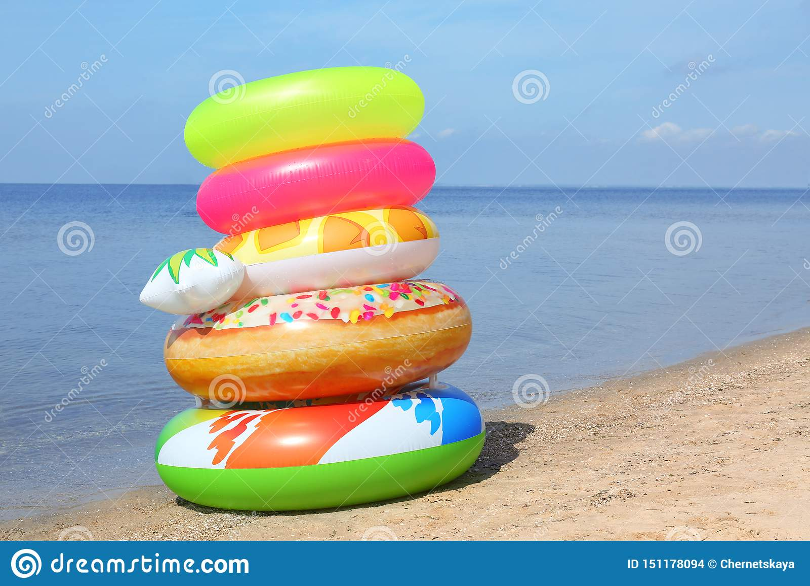堆在沙滩的不同的明亮的可膨胀的圆环在海附近