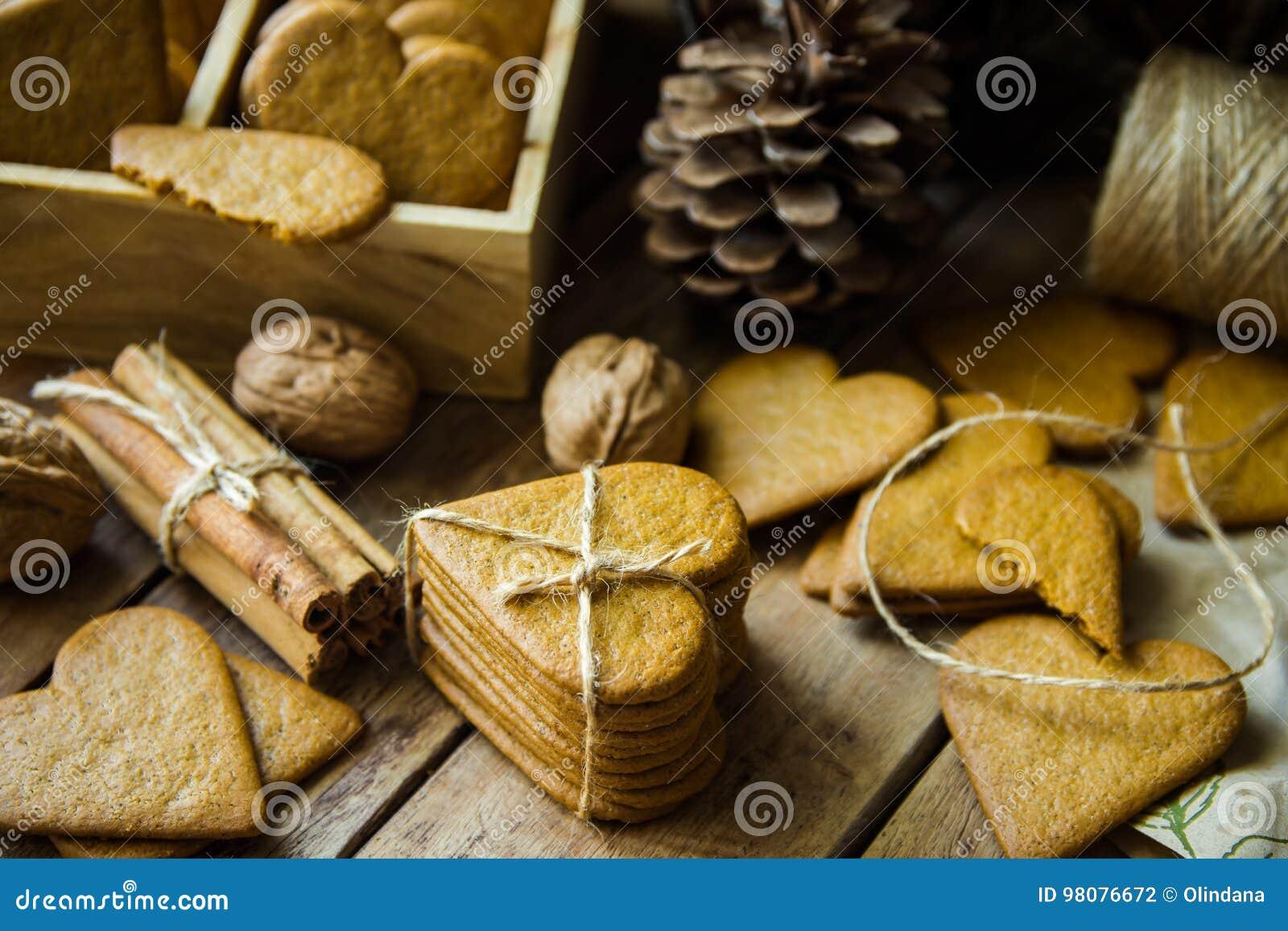 堆姜饼在心脏形状的圣诞节曲奇饼栓与麻线,肉桂条,坚果,在木厨房用桌上的杉木锥体