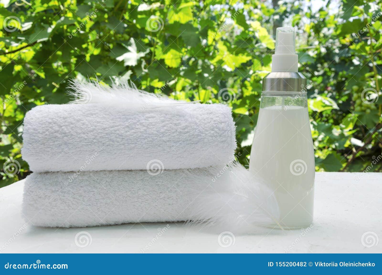 堆白色毛巾,玻璃瓶软化剂和羽毛作为精美洗涤物的标志