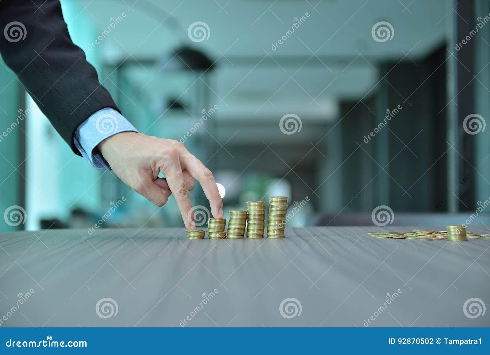 堆积硬币按增长的顺序的商人在书桌