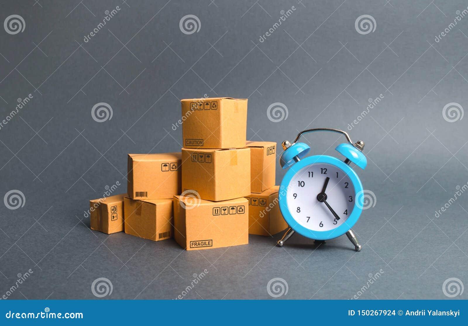 堆纸板箱和一个蓝色闹钟 快递概念 临时储藏、有限的提议和折扣