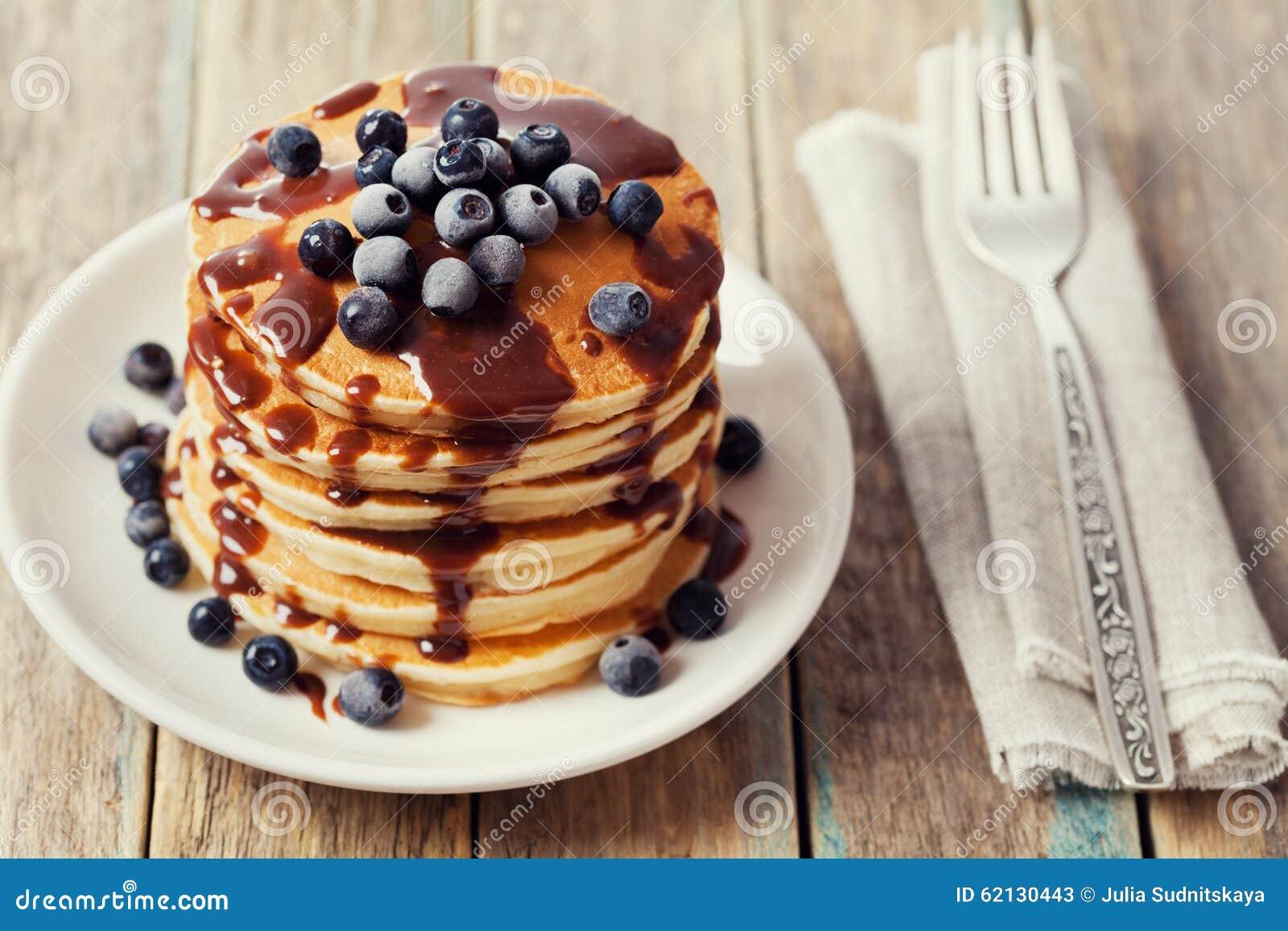 堆薄煎饼或油炸馅饼用巧克力汁和冷冻蓝莓在一块白色板材在一张木土气桌上