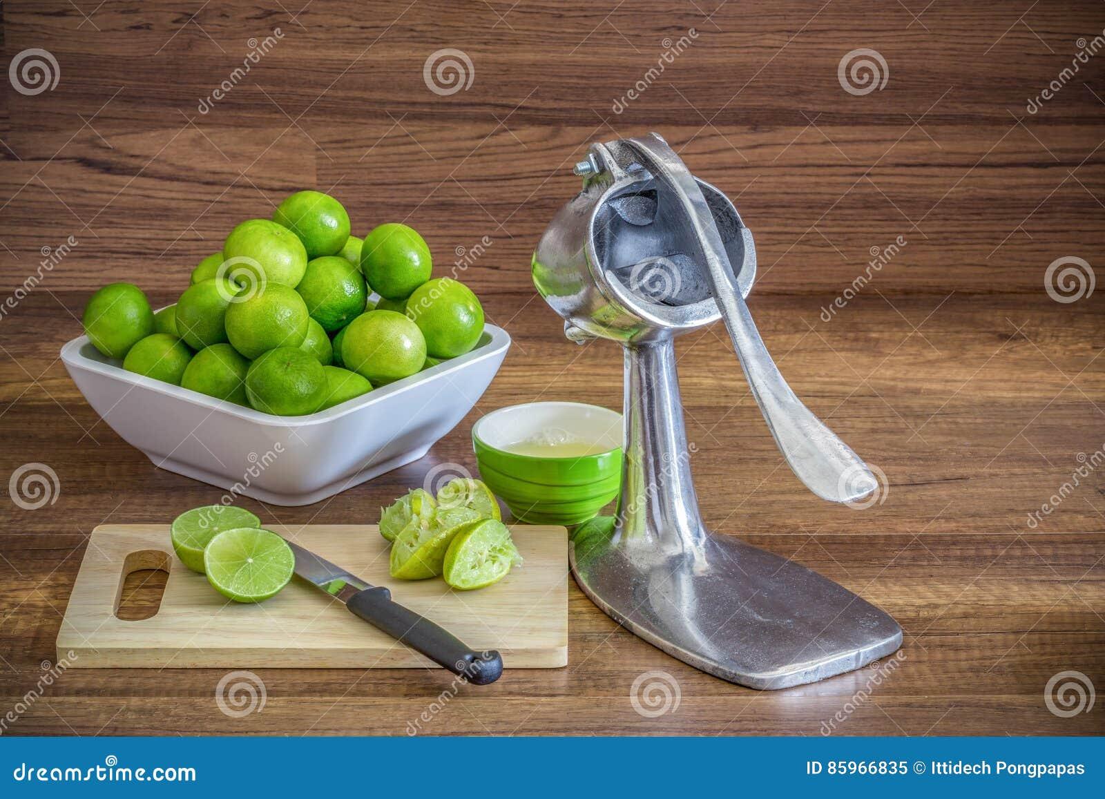 堆绿色柠檬用铝手工榨汁器剥削者果子