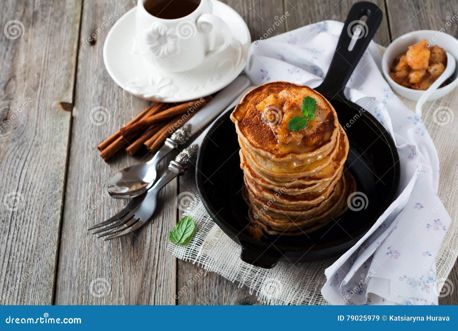 堆从荞麦面粉的薄煎饼用被烘烤的苹果和桂香在老木背景 健康的早餐