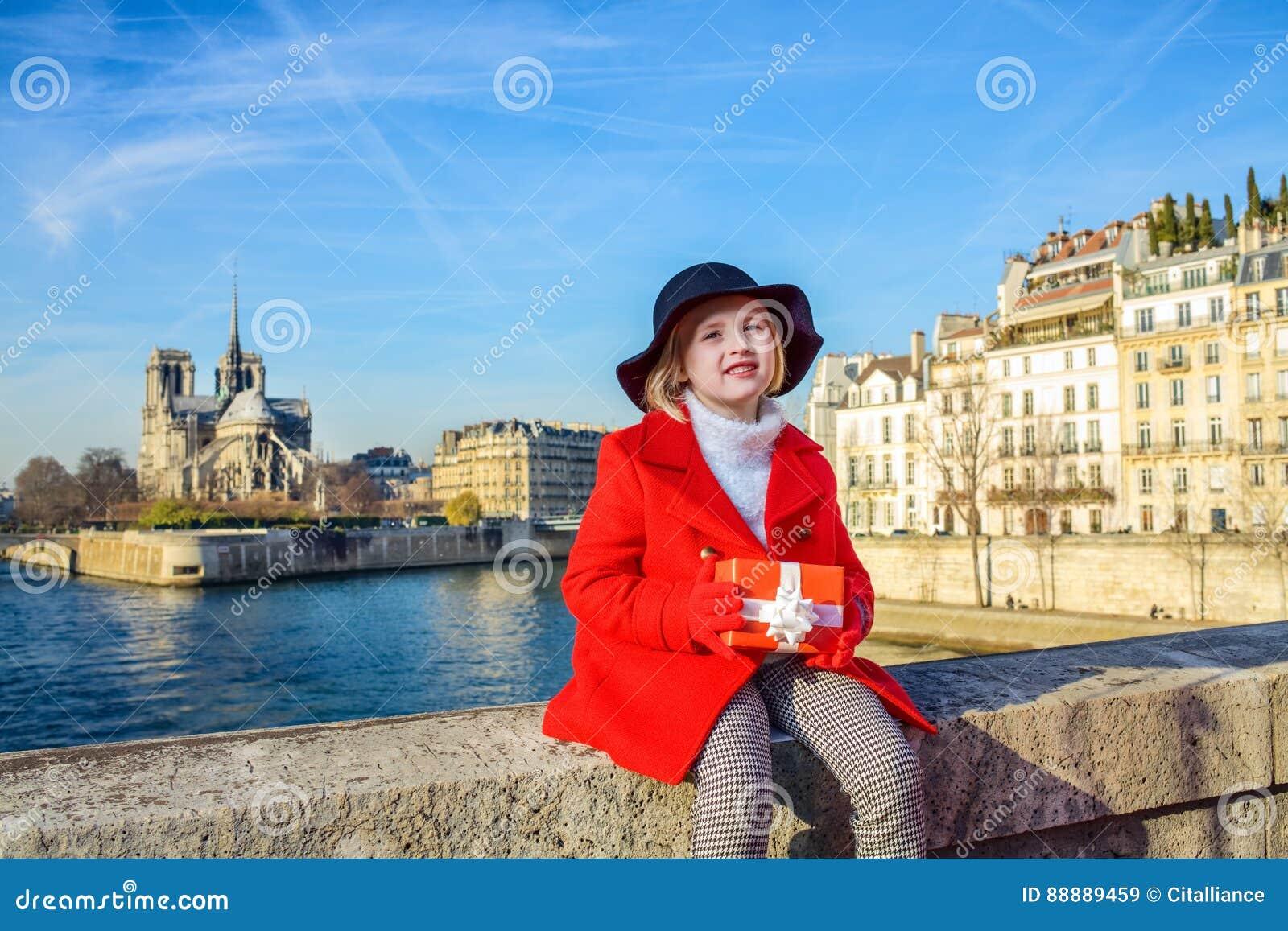 堤防的女孩在有圣诞节礼物的巴黎圣母院附近