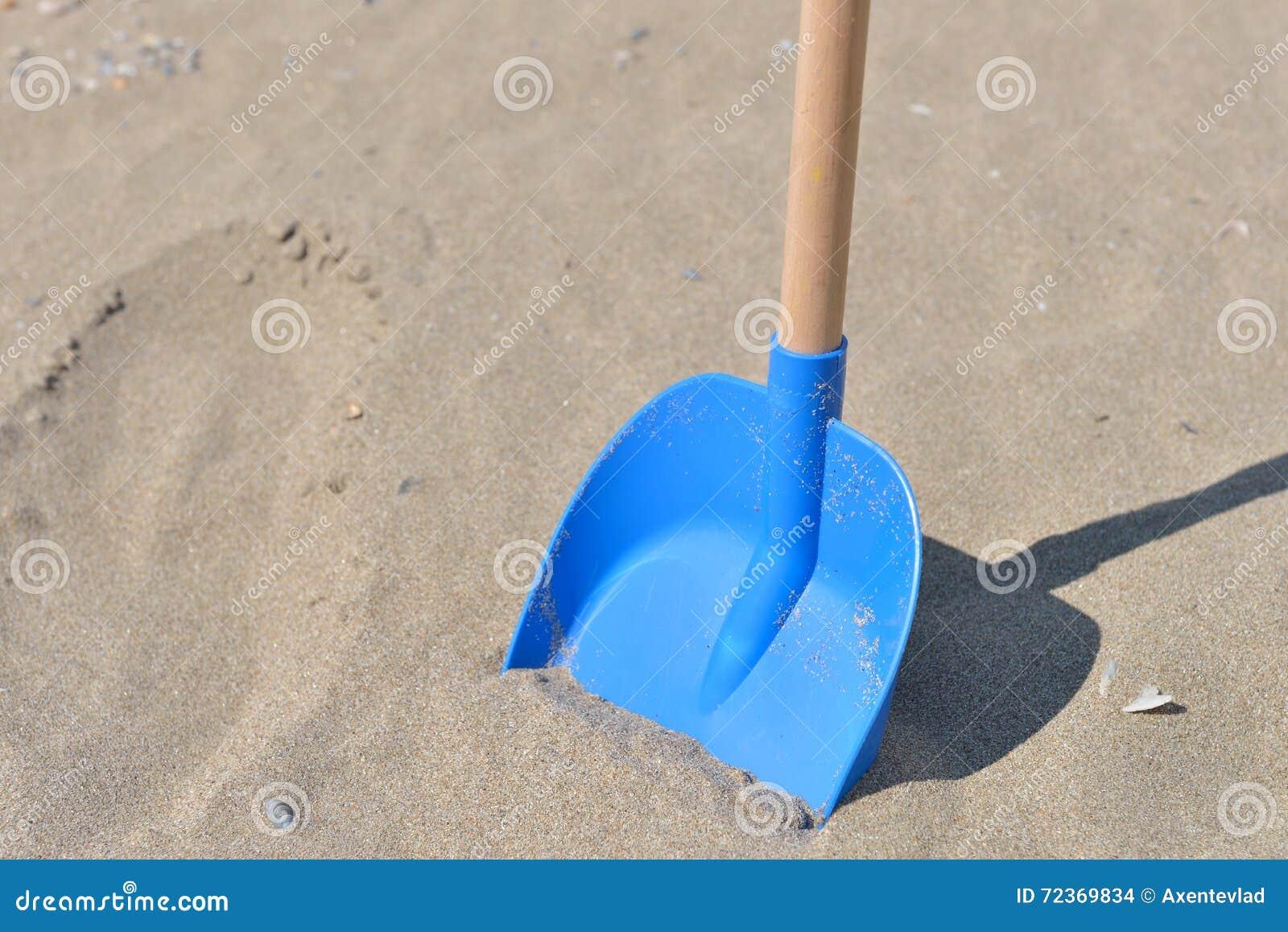 从塑料的蓝色铁锹与孩子的木尾巴在a的沙子
