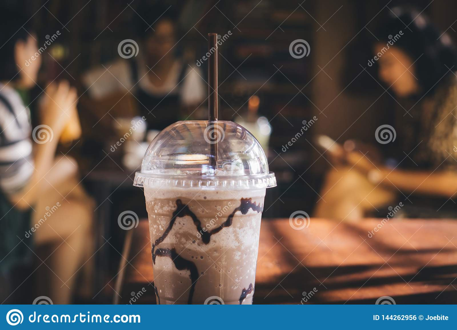 塑料被冰的巧克力杯子选择聚焦有有人的交谈,弹吉他,读书和享用
