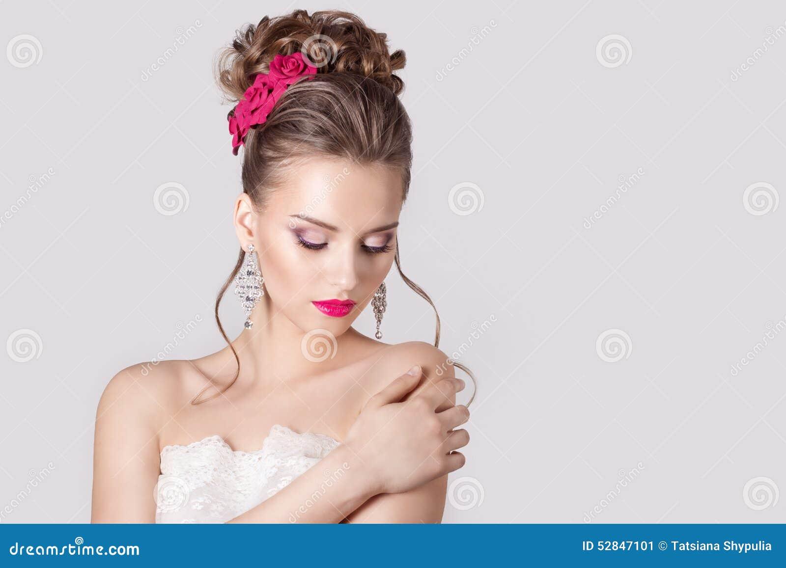 塑造一个美丽的可爱的女孩的画象有一个高柔和的典雅的晚上婚礼的发型和明亮的构成的与流程