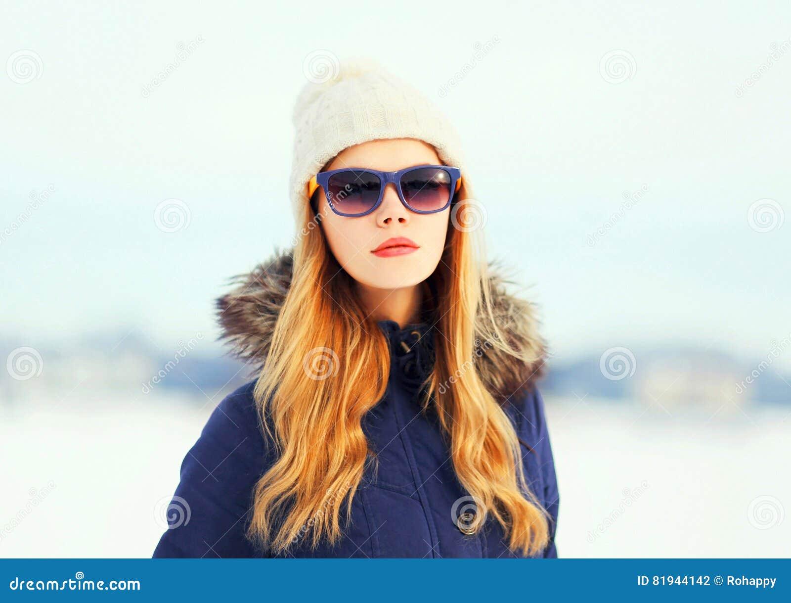 塑造冬天画象相当白肤金发的妇女佩带的夹克帽子太阳镜