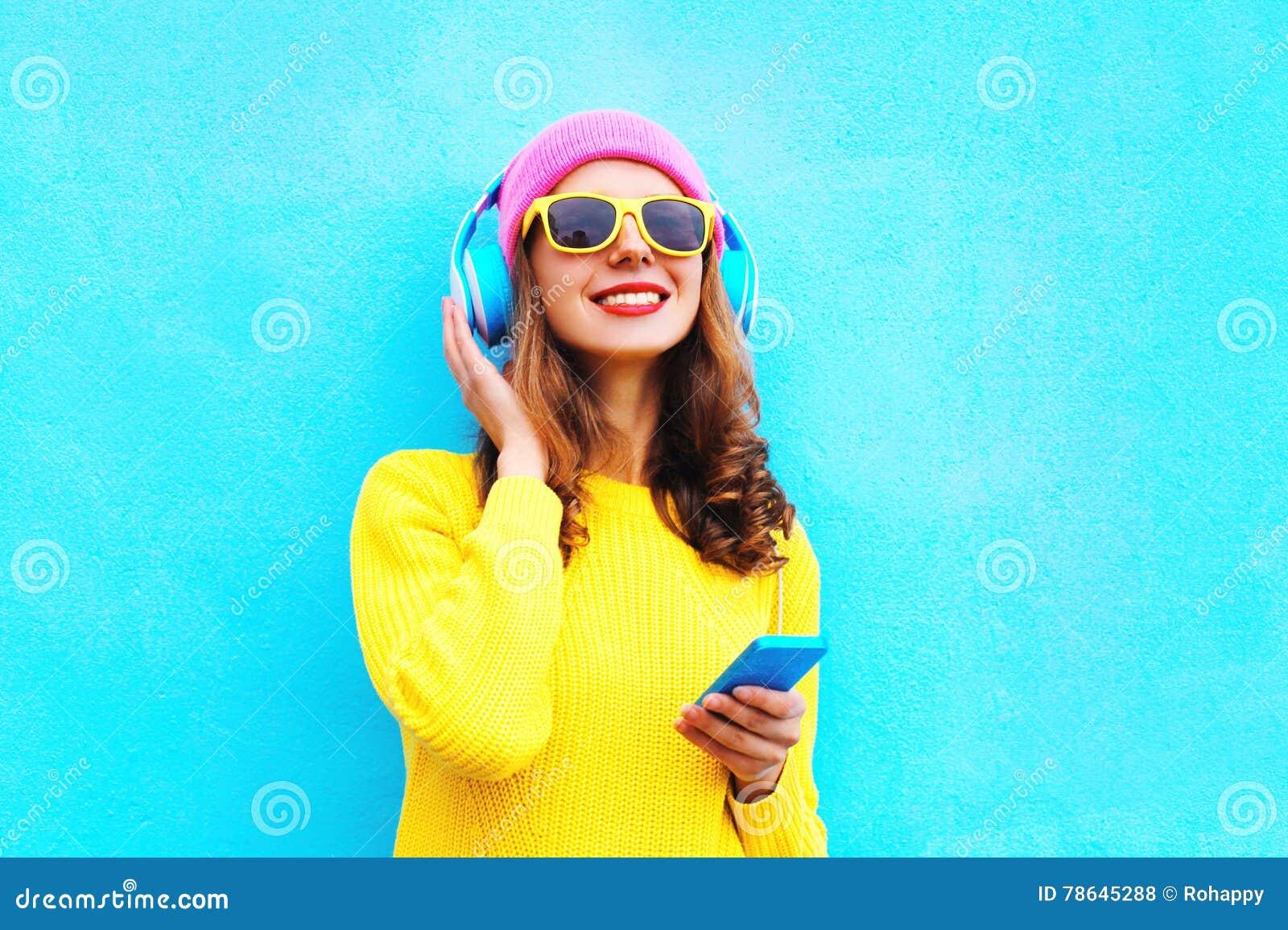 塑造相当听到在耳机的音乐的甜无忧无虑的女孩有戴五颜六色的桃红色帽子黄色太阳镜的智能手机的