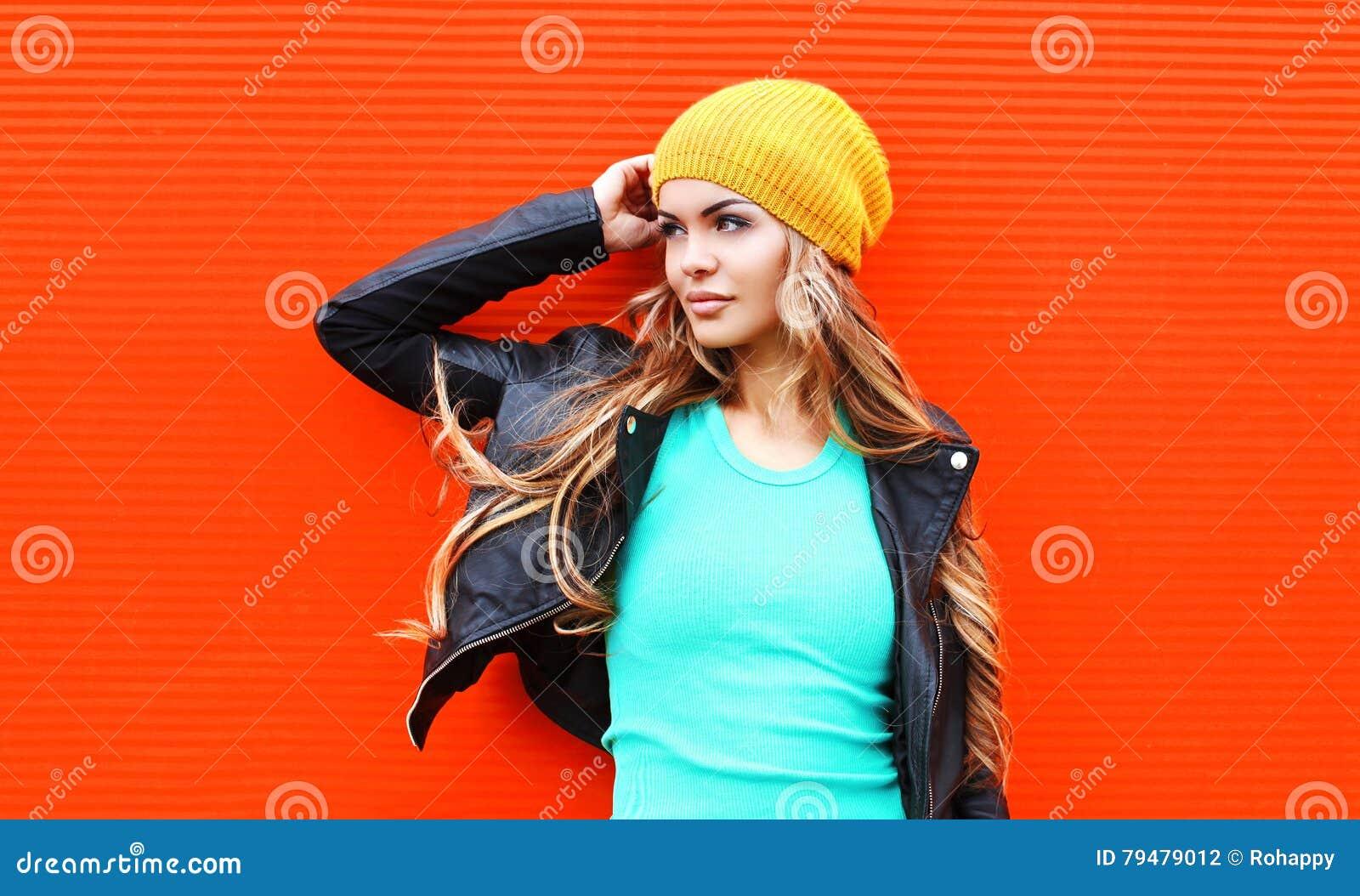 塑造相当年轻白肤金发的看在五颜六色的红色的外形的妇女佩带的夹克帽子