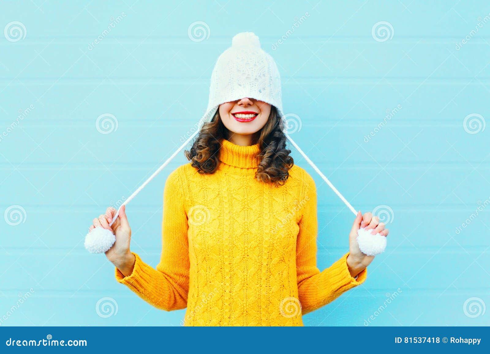 塑造被编织的获得帽子和的毛线衣的愉快的少妇在五颜六色的蓝色的乐趣