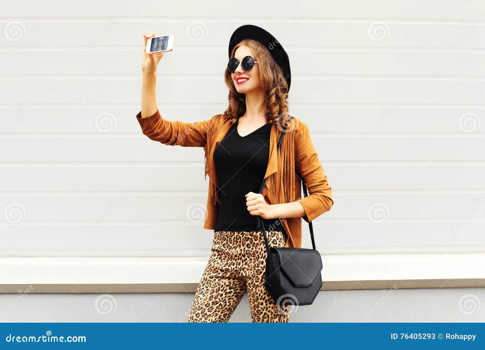 塑造采取照片在智能手机的愉快的年轻微笑的妇女图片自画象戴减速火箭的典雅的帽子,太阳镜