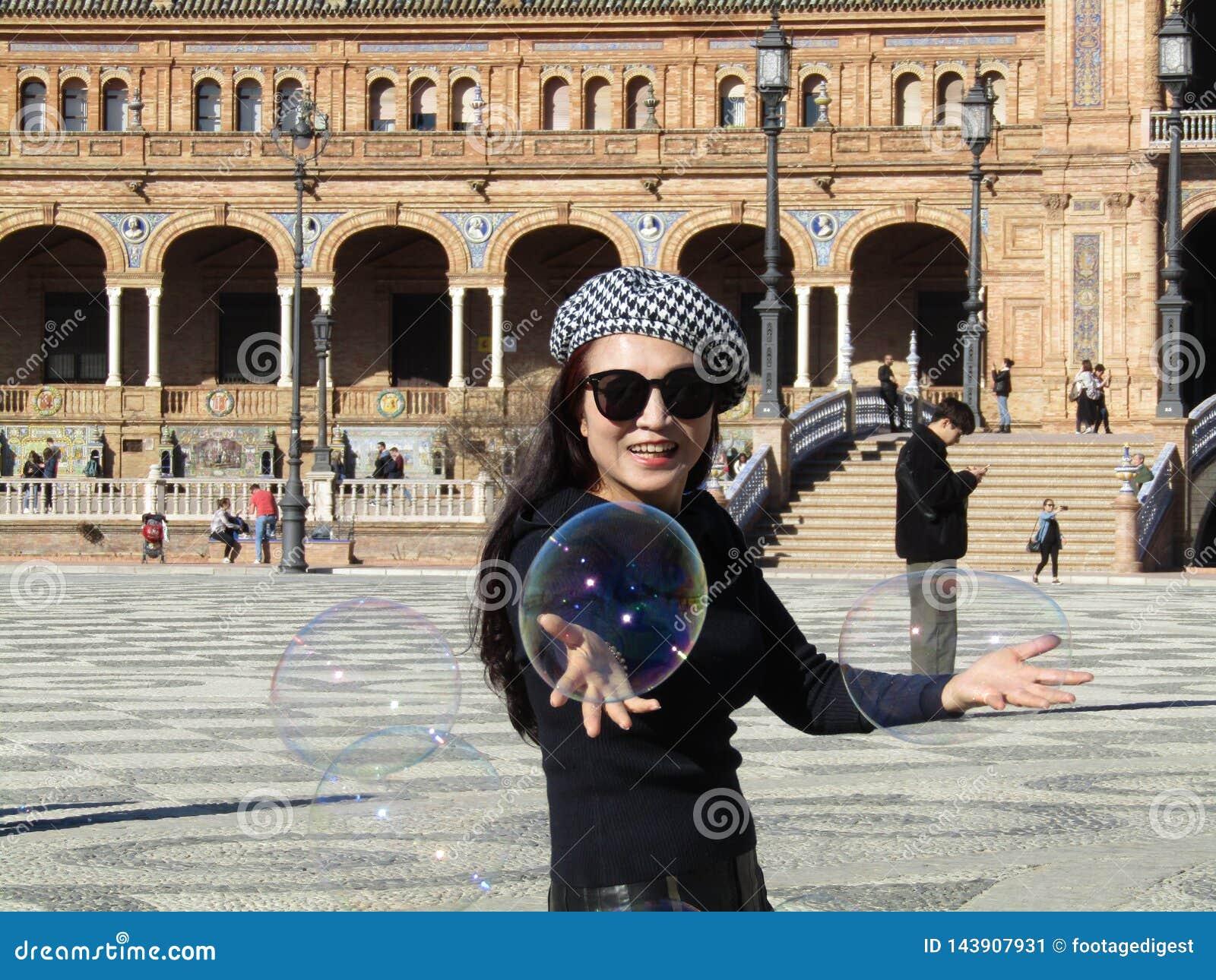 塞维利亚,西班牙- 2019年1月26日:女孩吹大肥皂泡