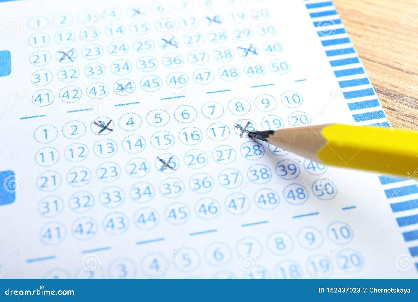 填好彩票用在木桌上的铅笔,特写镜头