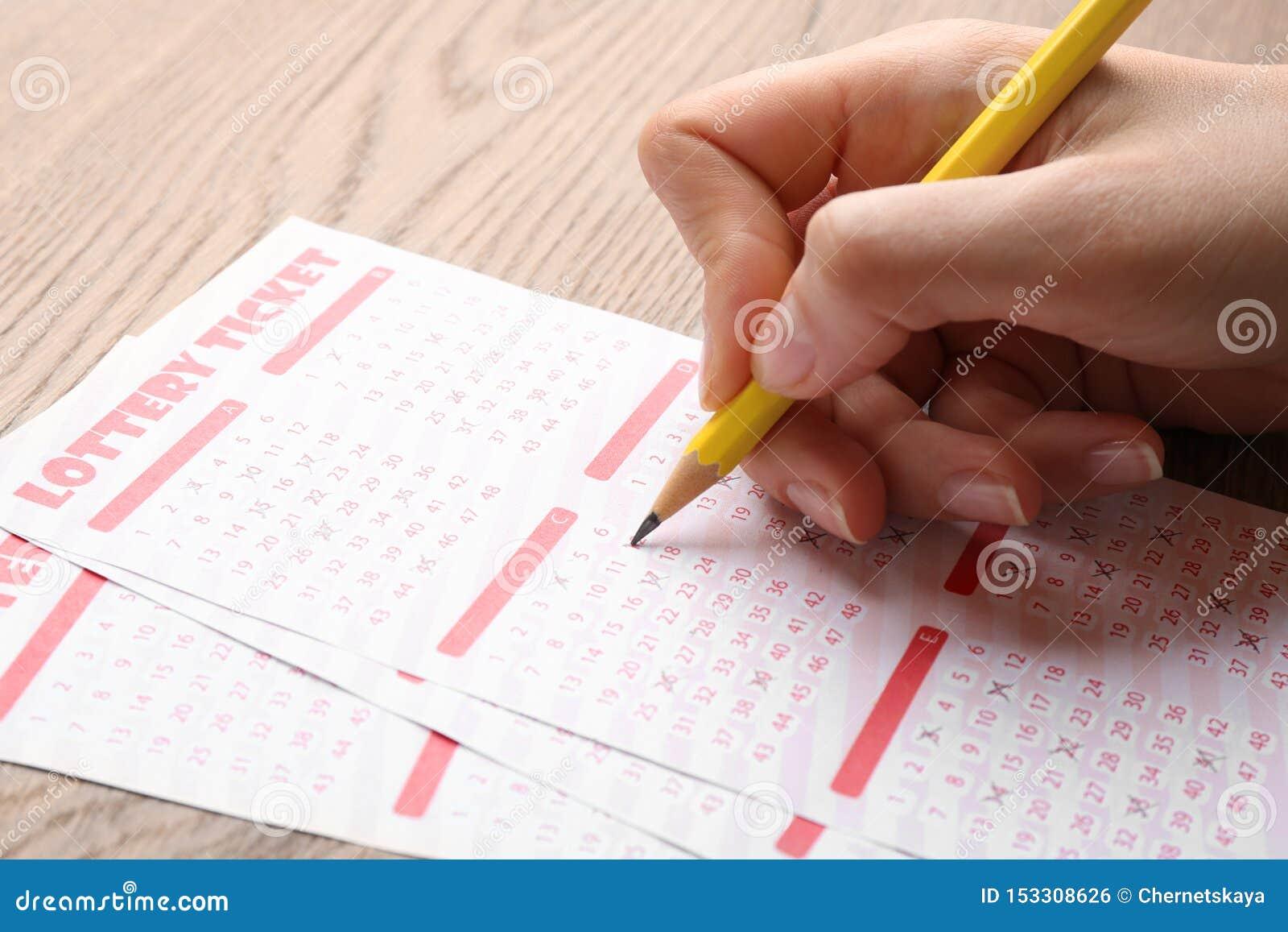填好彩票的妇女用在桌,特写镜头上的铅笔 r