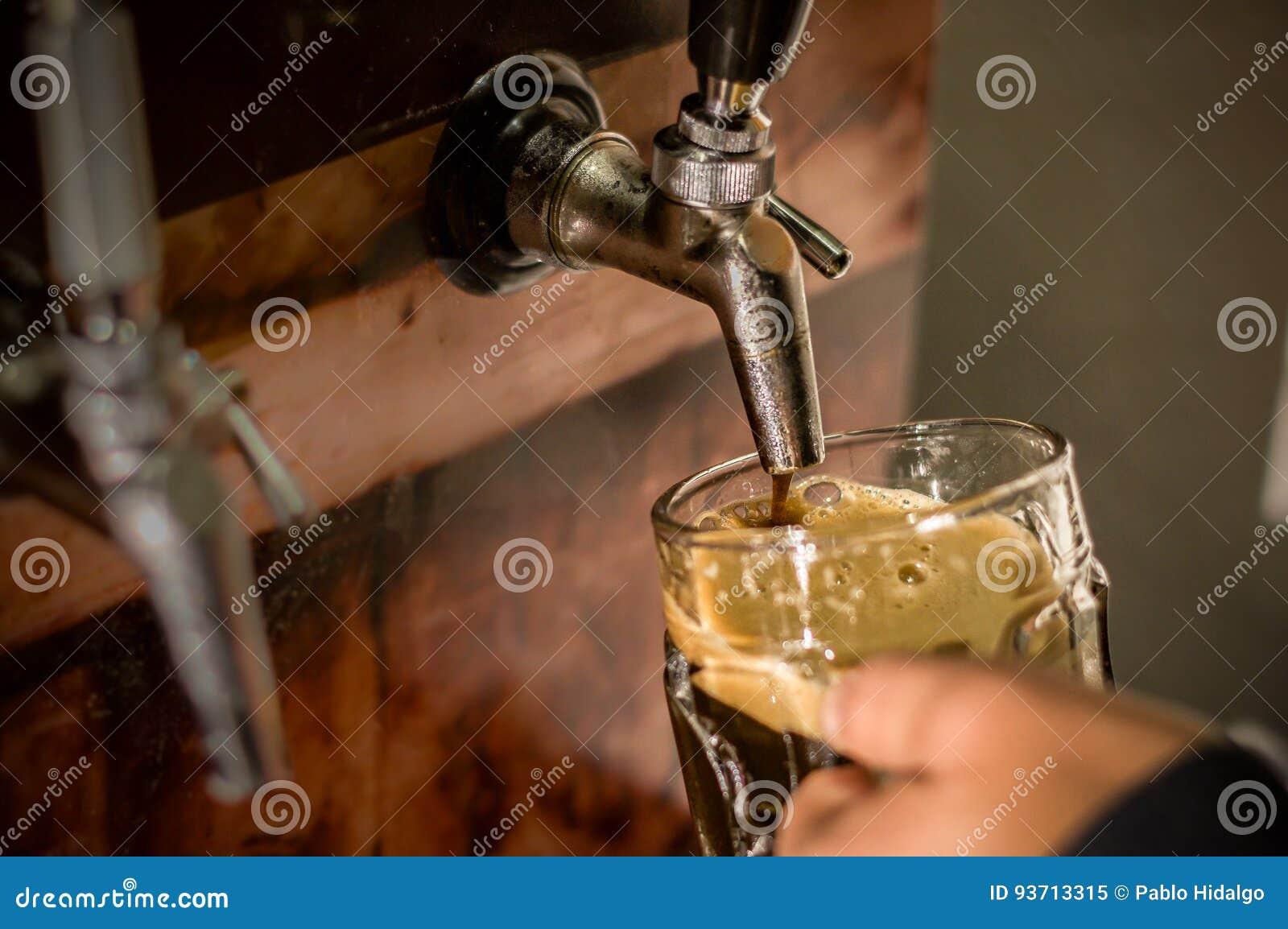 填满用工艺啤酒每品脱玻璃的侍酒者