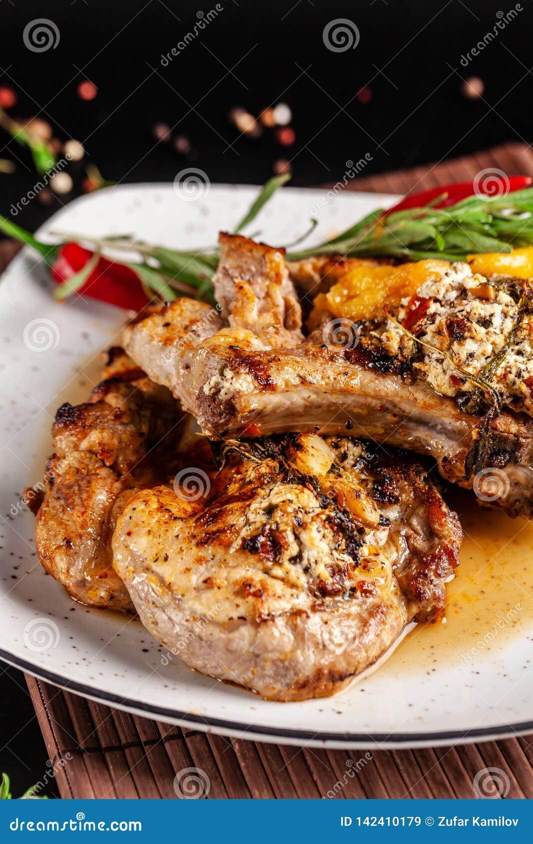 墨西哥烹调的概念 烤猪肉牛排用辣调味汁、红辣椒辣调味汁、桃子和虾 美丽的服务
