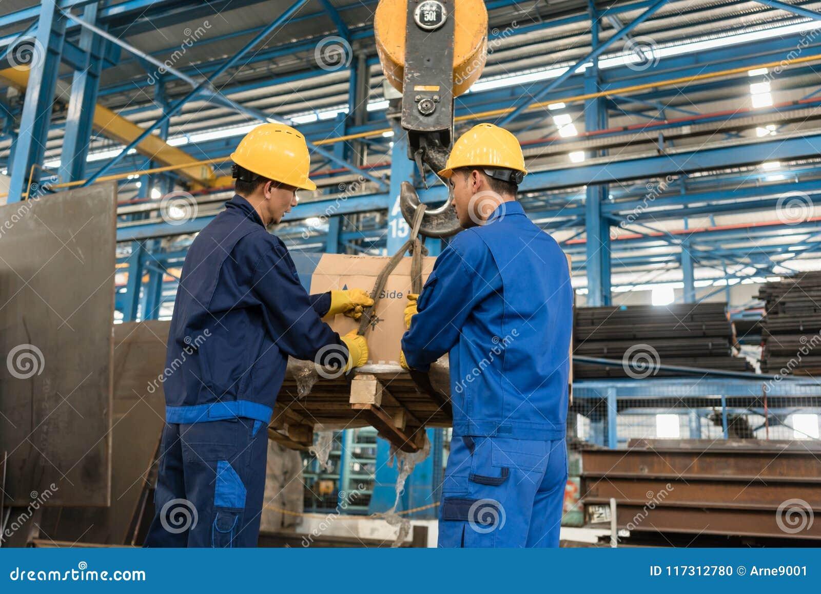 处理重的装货的两名工作者举被起重机