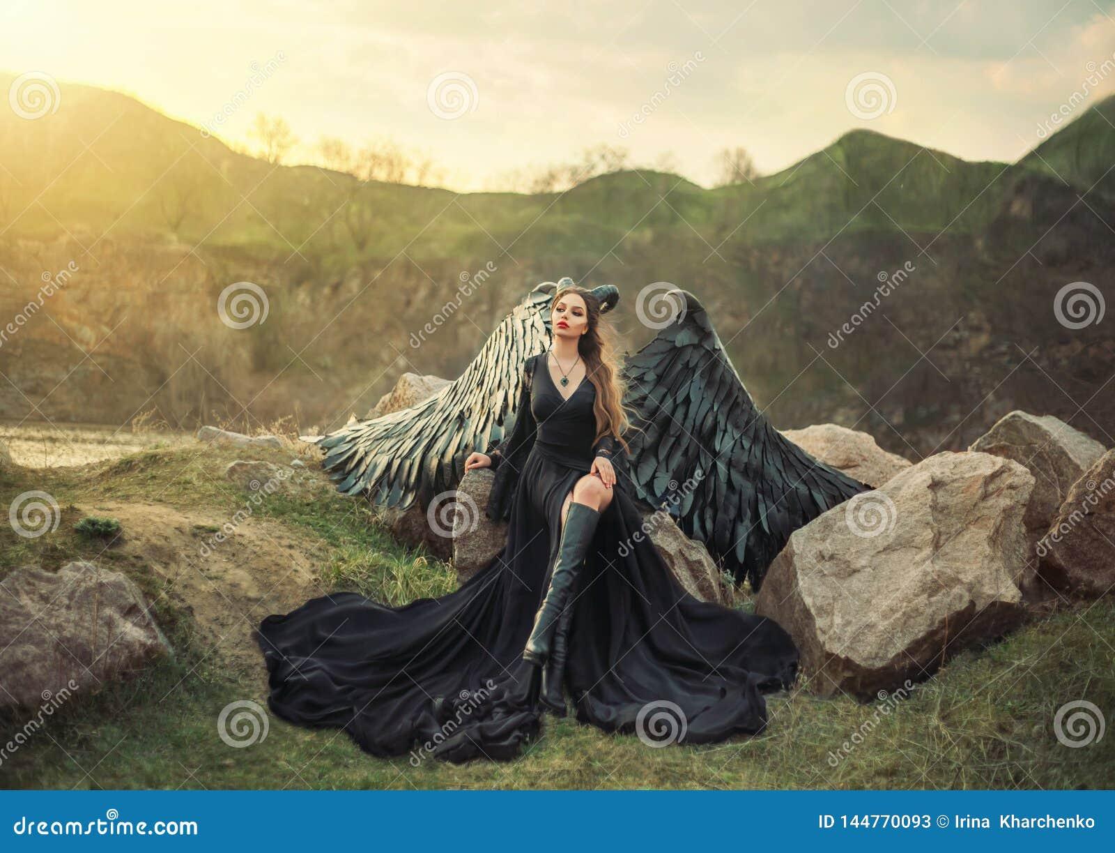 复兴的面貌古怪的人,夜观看的日出的女王/王后,长的轻的黑礼服的女孩有黑羽毛翼的坐岩石