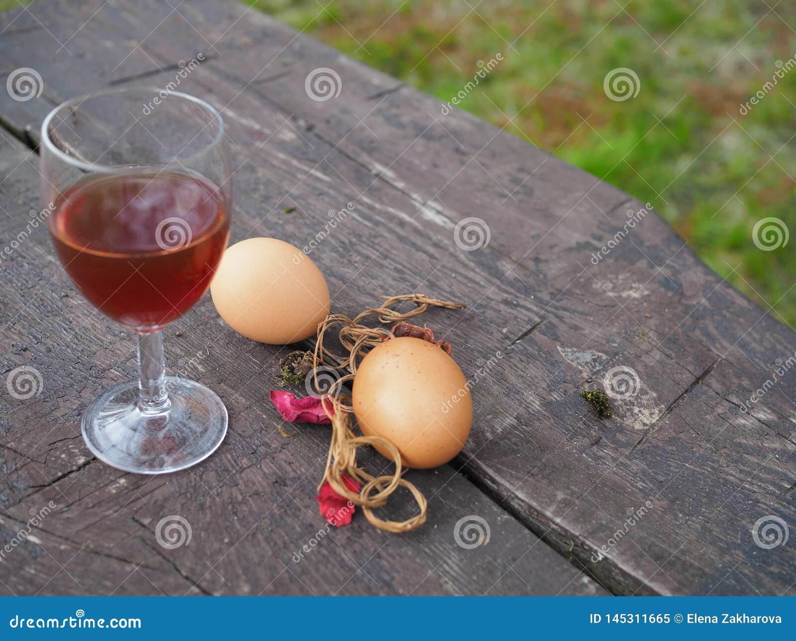 复活节彩蛋和杯在桌上的红酒
