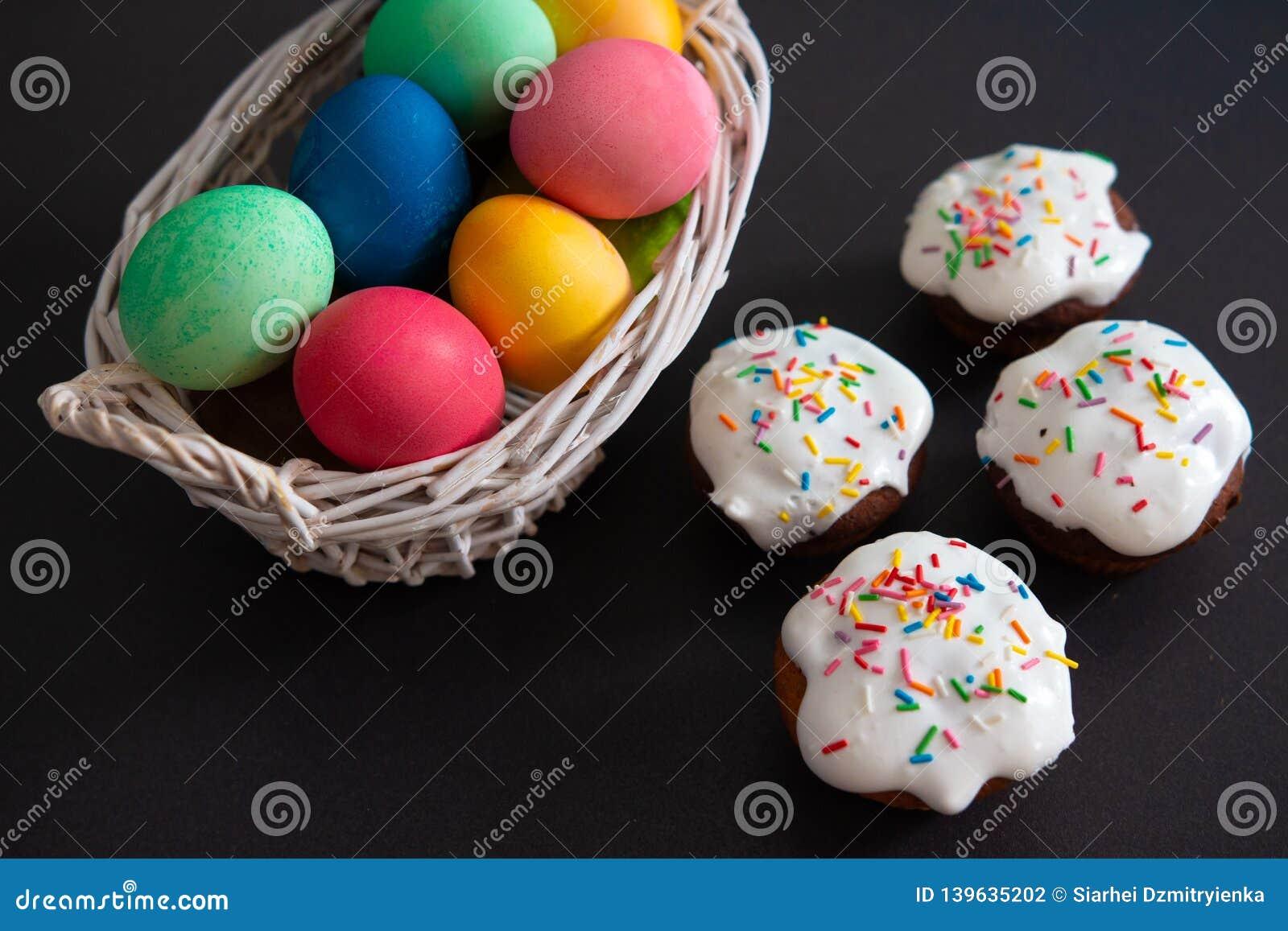 复活节杯形蛋糕和五颜六色的被绘的鸡蛋