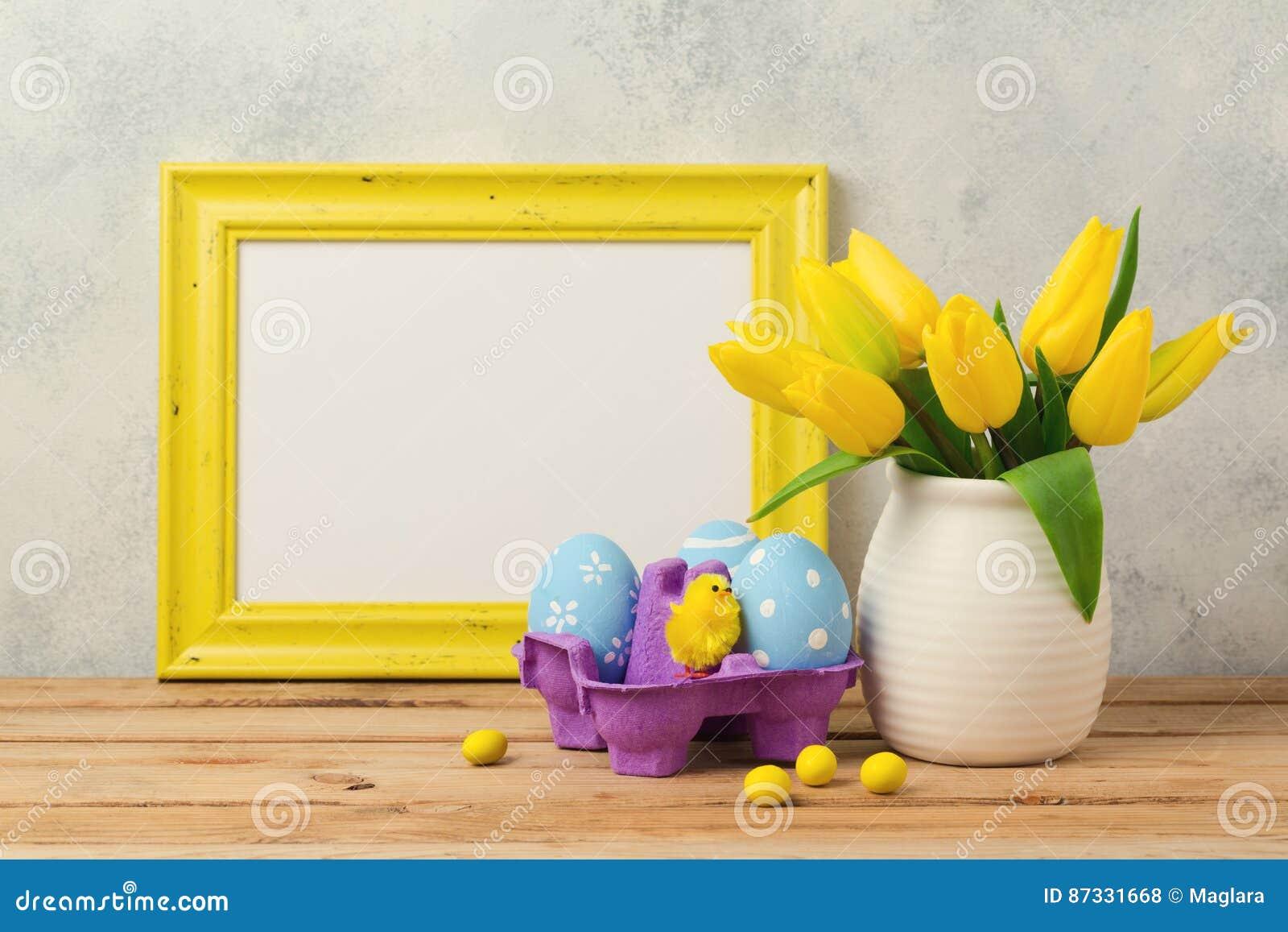 复活节与郁金香花、蛋装饰和空白的照片框架的假日概念