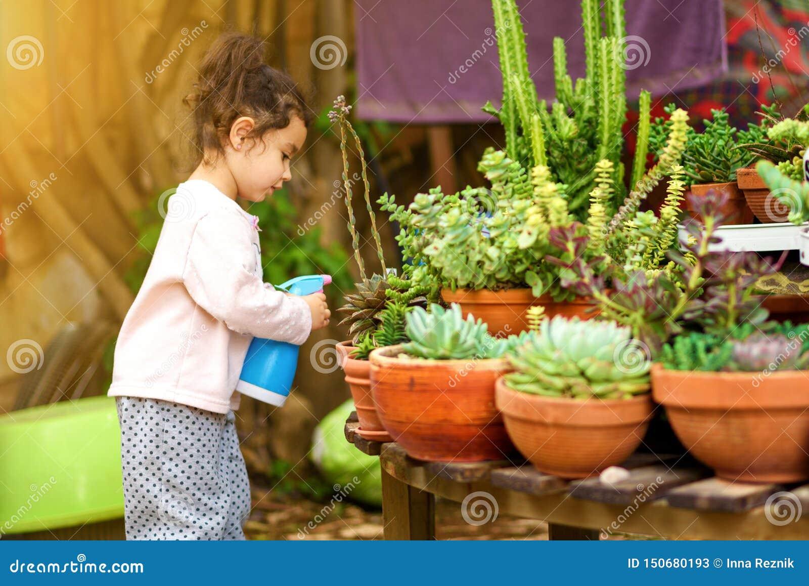 夏天乐趣:一点美女浇灌的庭院