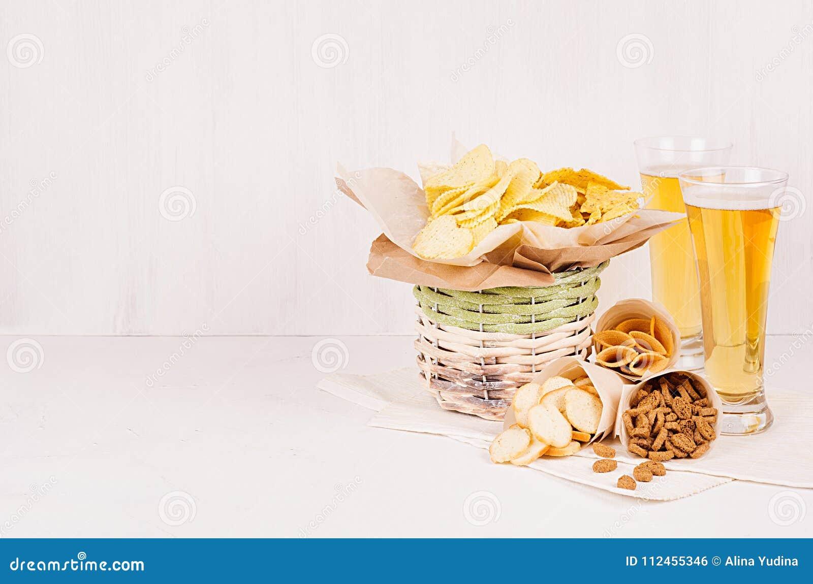 夏天快餐和储藏啤酒在玻璃-烤干酪辣味玉米片、油煎方型小面包片、芯片、玉米粉薄烙饼在土气篮子和纸角落在白色木backgr