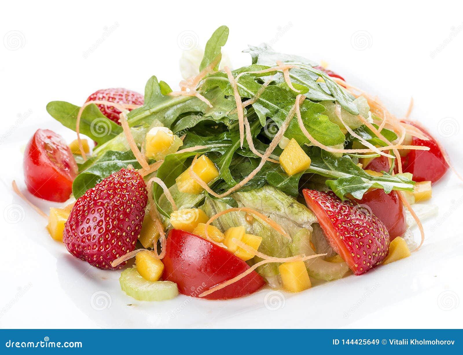 夏天沙拉用草莓和蕃茄 在一块白色板材上
