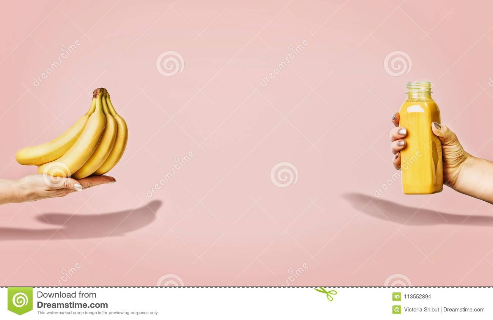 夏天食物和饮料背景用香蕉和黄色饮料瓶在女性手上在粉红彩笔