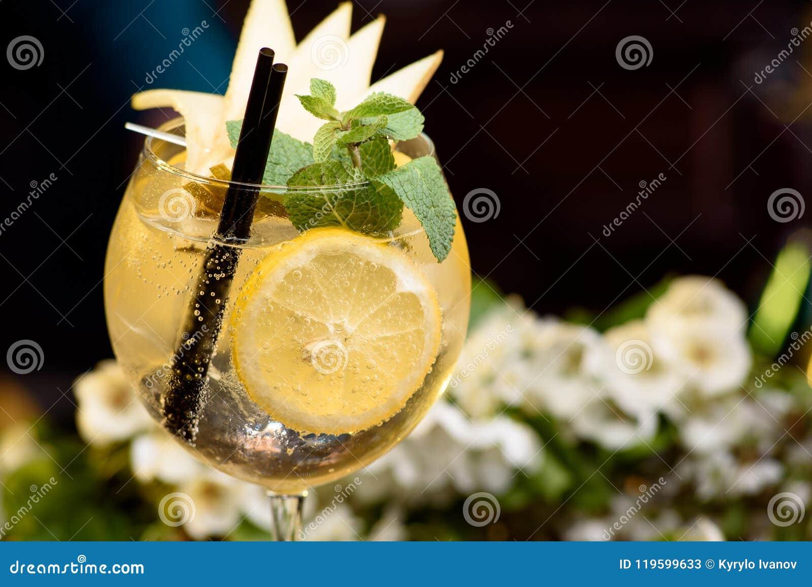 夏天鸡尾酒装饰用在一张木桌上的薄菏、柠檬和切片梨在花卉背景