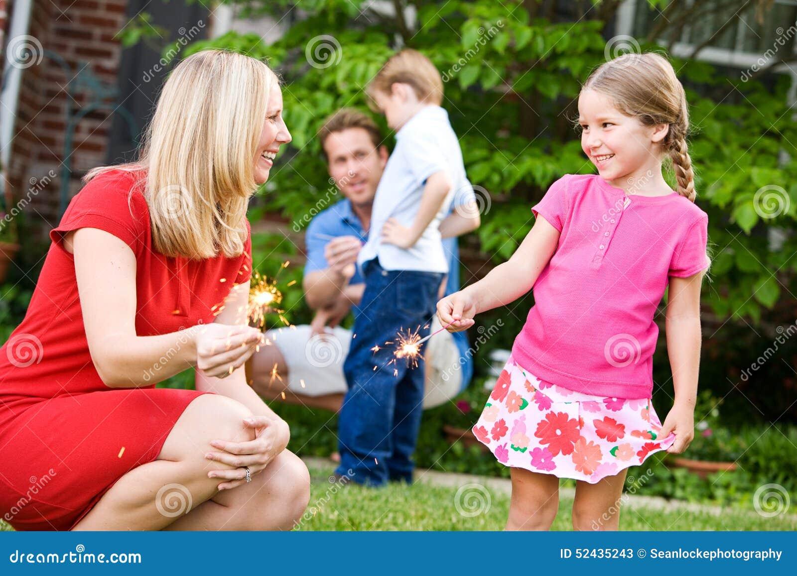 夏天:妈妈教女孩拿着闪烁发光物