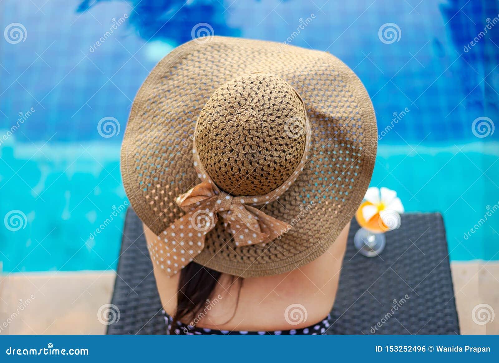 夏时和假期 松弛妇女的生活方式和饮用的汁液桔子很愉快在豪华游泳场sunbath