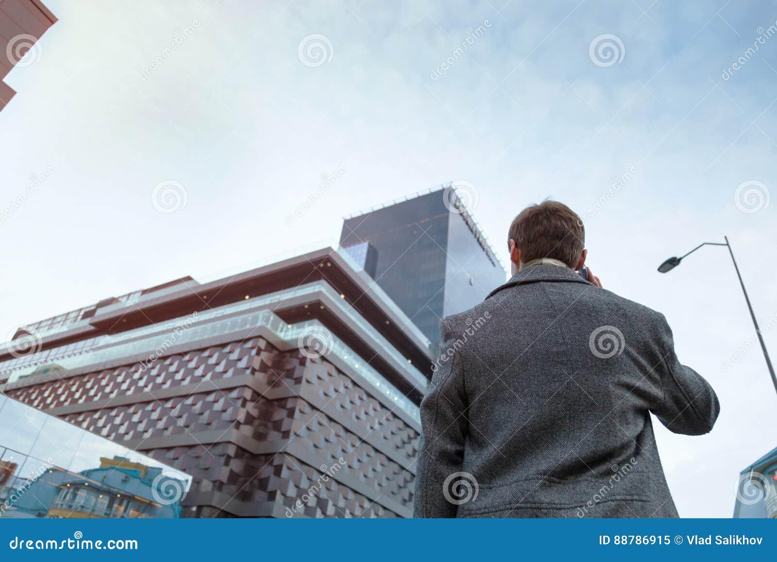 外套的一个年轻人打站立在商业中心附近的一个匿名电话