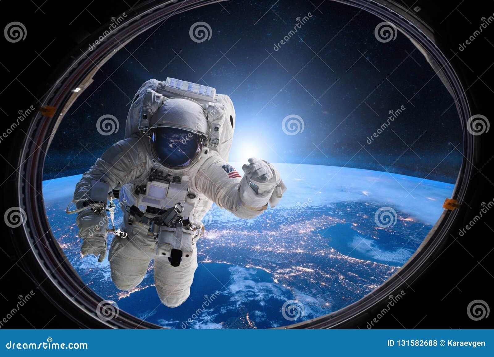 外层空间的宇航员从在地球的背景的舷窗 美国航空航天局装备的这个图象的元素
