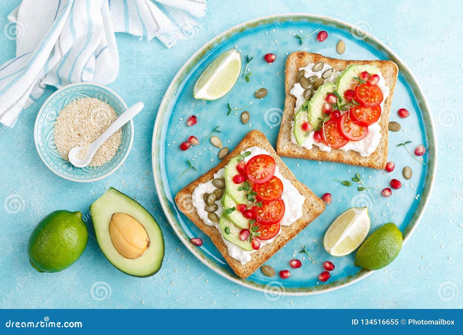 多士用希腊白软干酪、蕃茄、鲕梨、石榴、南瓜籽和亚麻新芽 健康饮食的早餐可口和