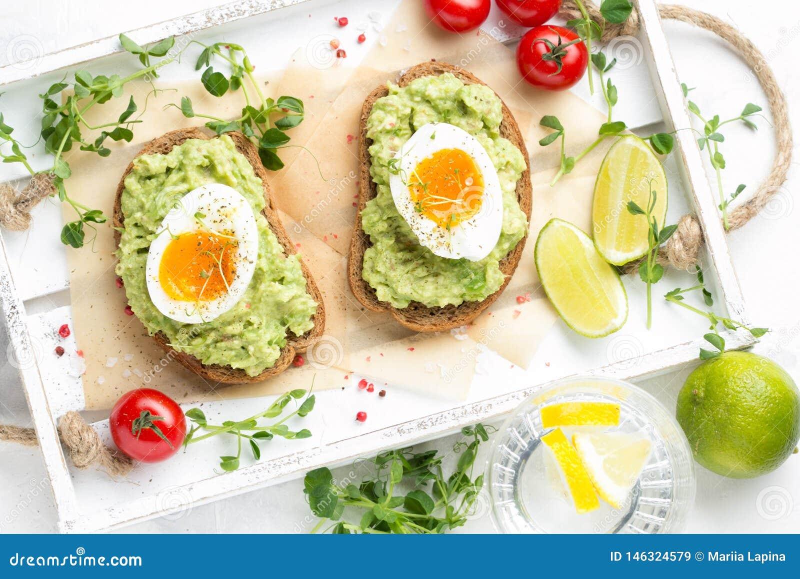 多士用鲕梨纯汁浓汤和水煮蛋在白色盘子,液体卵黄质,可口早餐,清淡的三明治 r