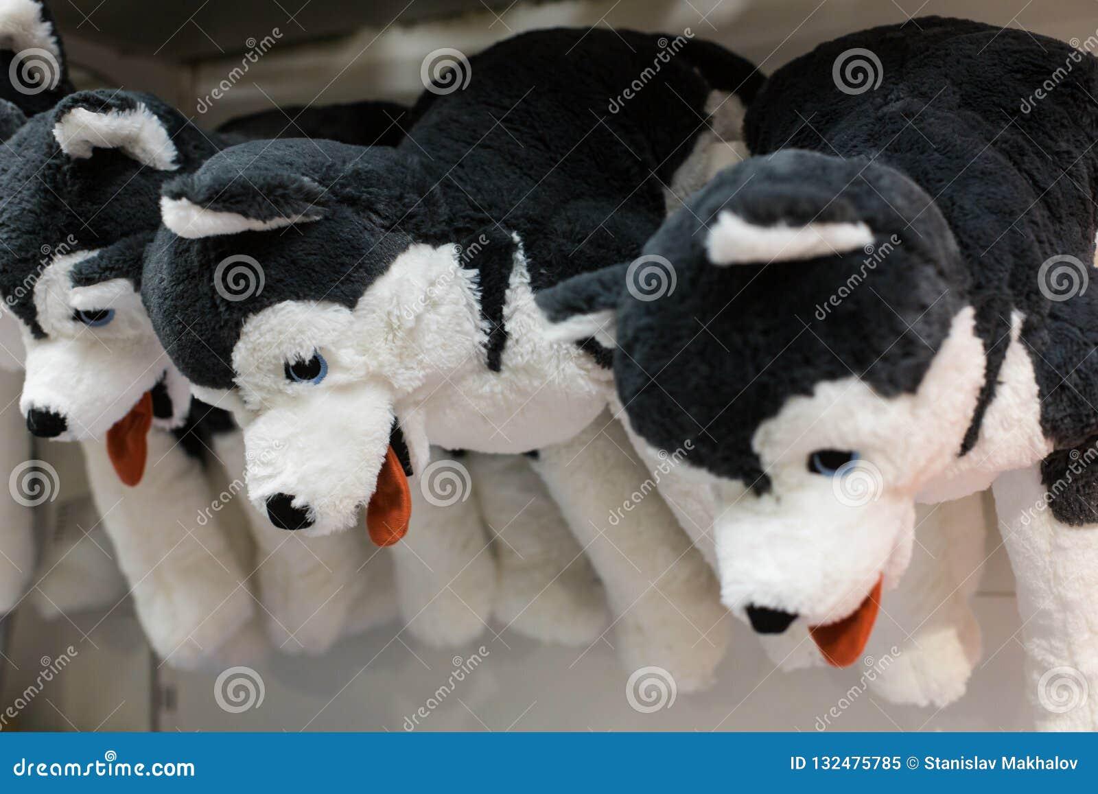 多壳的狗爱拥抱软的玩具从孩子的购物在礼品店的待售
