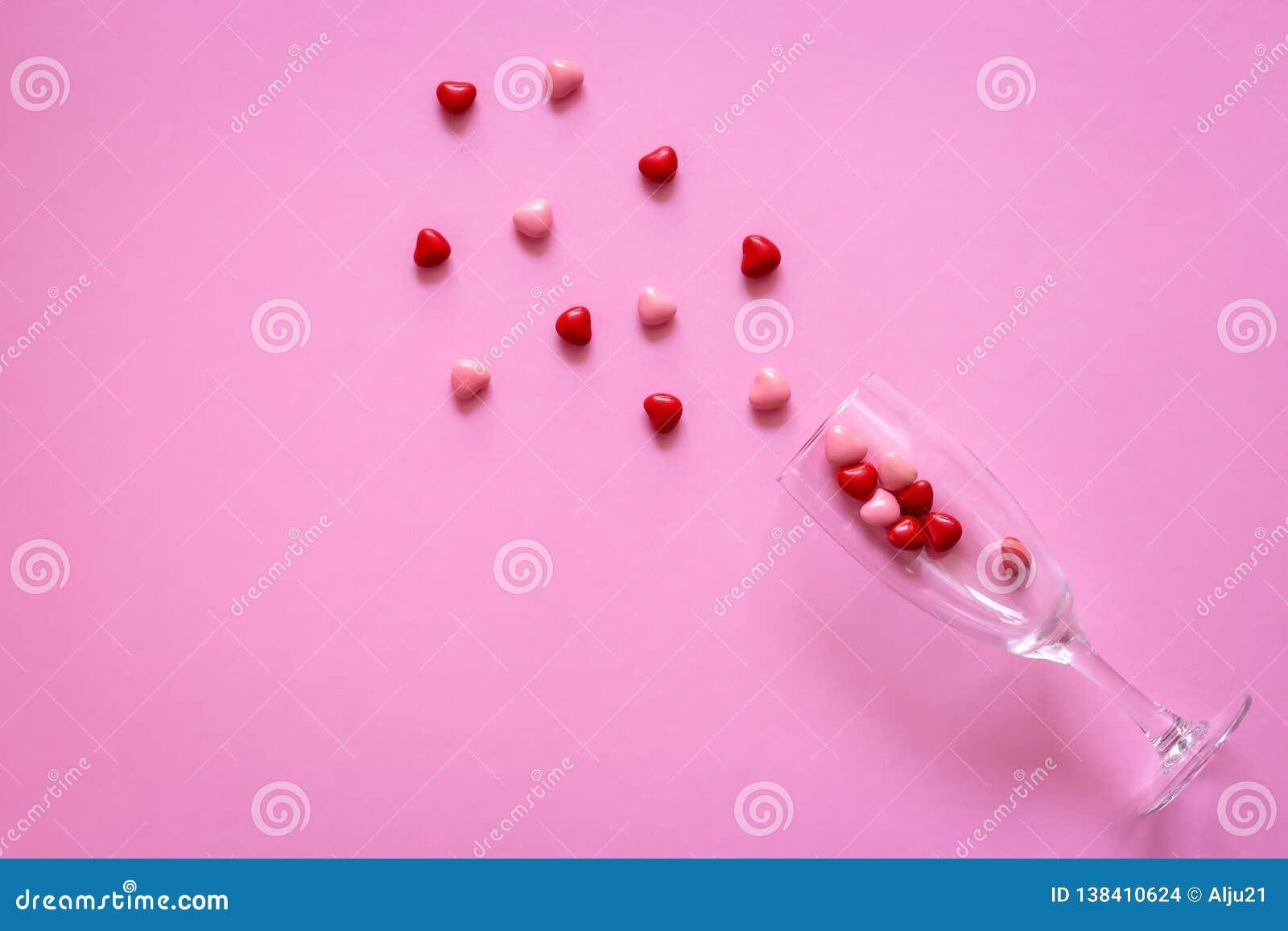 多彩多姿的糖果或药片以心脏的形式在酒杯 概念情人节或医学,药房,心脏病学