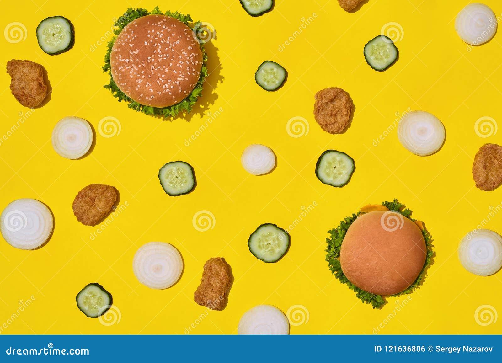 多数普遍的快餐 鸡块、汉堡用新鲜的黄瓜和葱在黄色背景顶视图