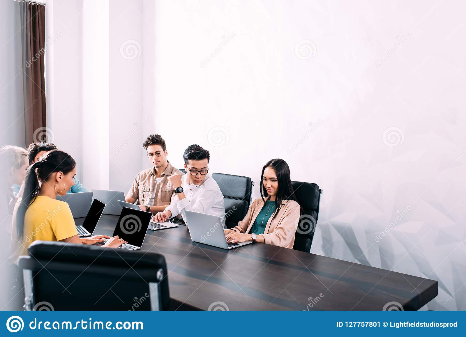 多文化商务伙伴开会议在与膝上型计算机的桌上在现代