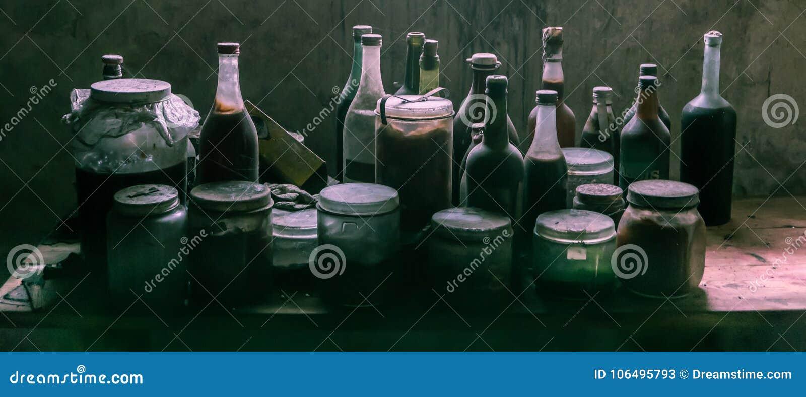 多灰尘的老玻璃瓶和罐头有可疑内容的
