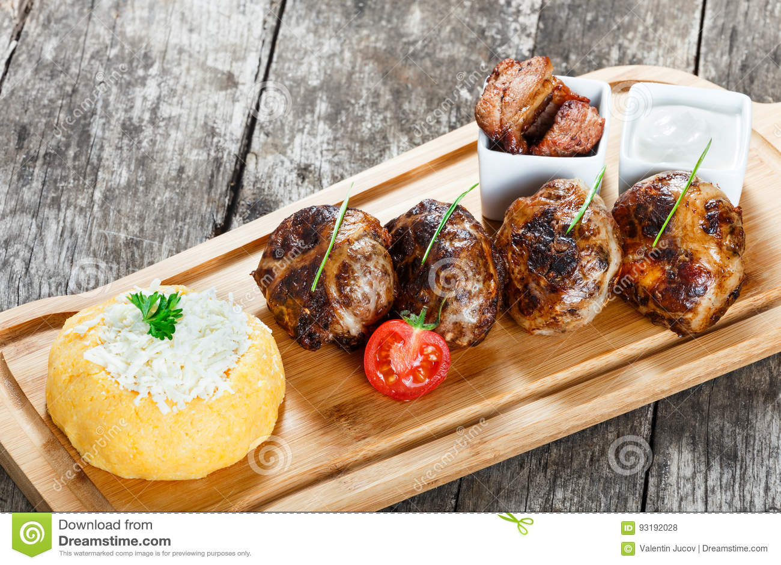 水多的可口肉炸肉排和碎玉米粥或者玉米粥麦片粥用在切板的山羊乳干酪在木背景