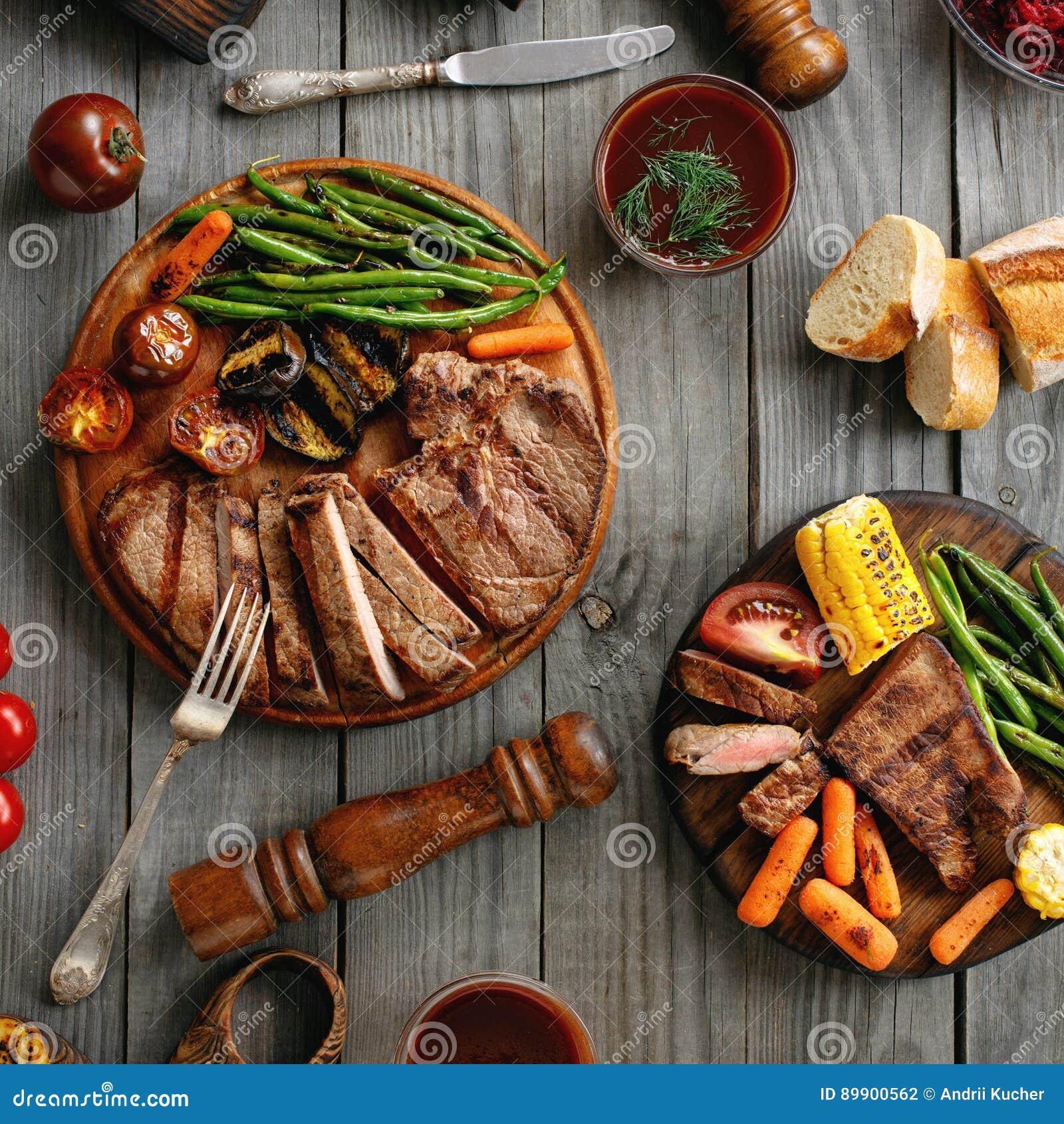 水多的牛排在与烤菜的一个格栅烹调了