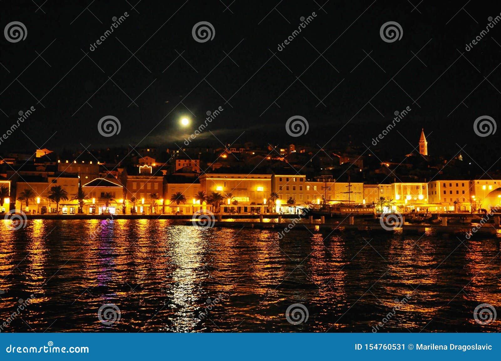 夜都市风景和沿海线与月亮在黑天空