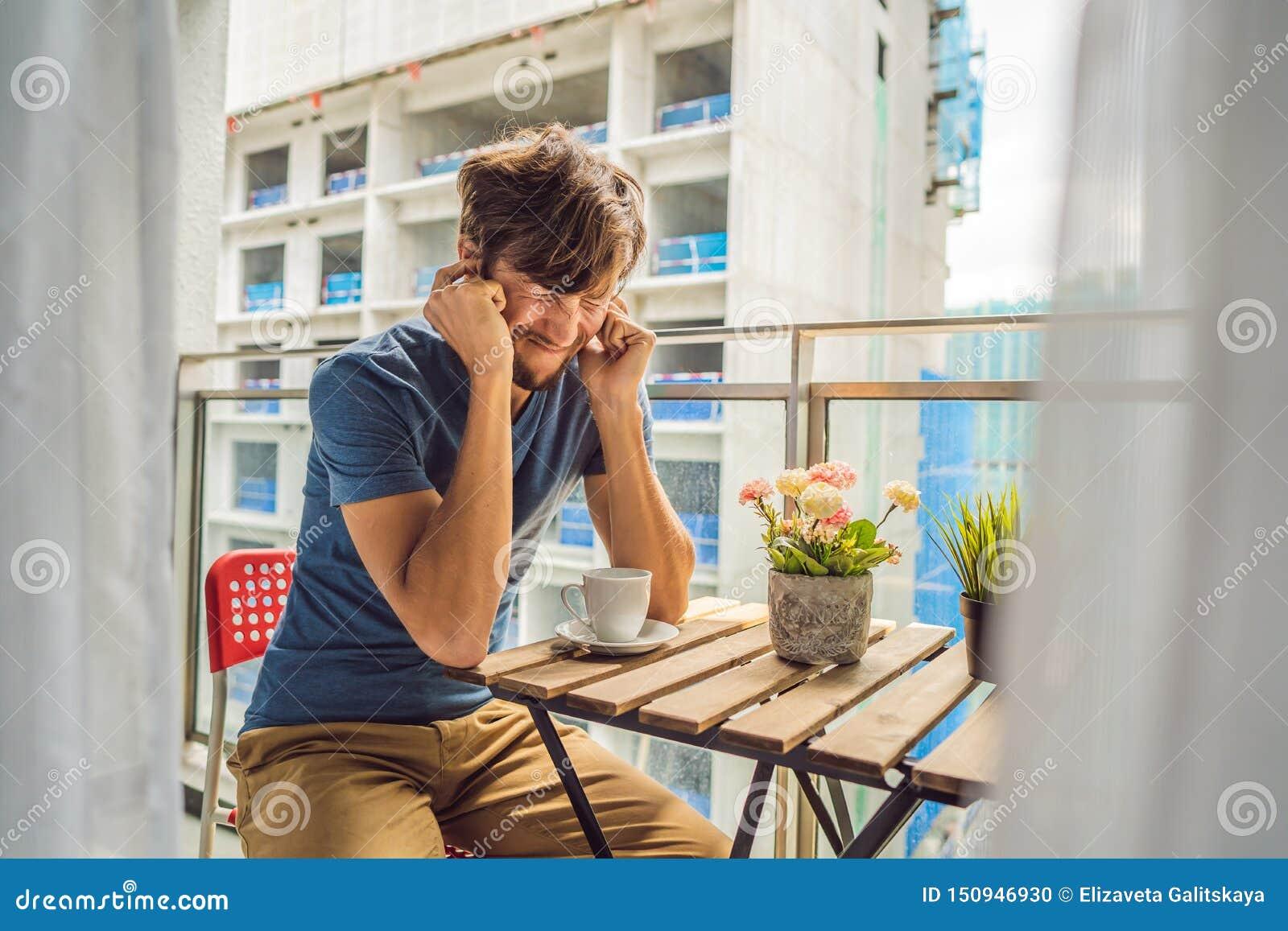 大厦工作懊恼的阳台的年轻人外面 噪声概念 从大厦尘土的空气污染